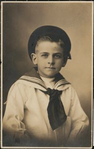 JP2011/1-3  A photographic postcard (silver gelatin print) depicting a portrait of a young boy, Harry Birkett Jnr., dressed in a sailor suit.   Annie Birkett was murdered by her second 'husband', a woman named Eugenia Falleni, in 1917. Falleni then allegedly attempted to murder Birkett's young son Harry. The case was a media sensation as it delved into the world of male impersonations and murder.  For full detail on this object refer to Collections Management Unit Vernon Database.